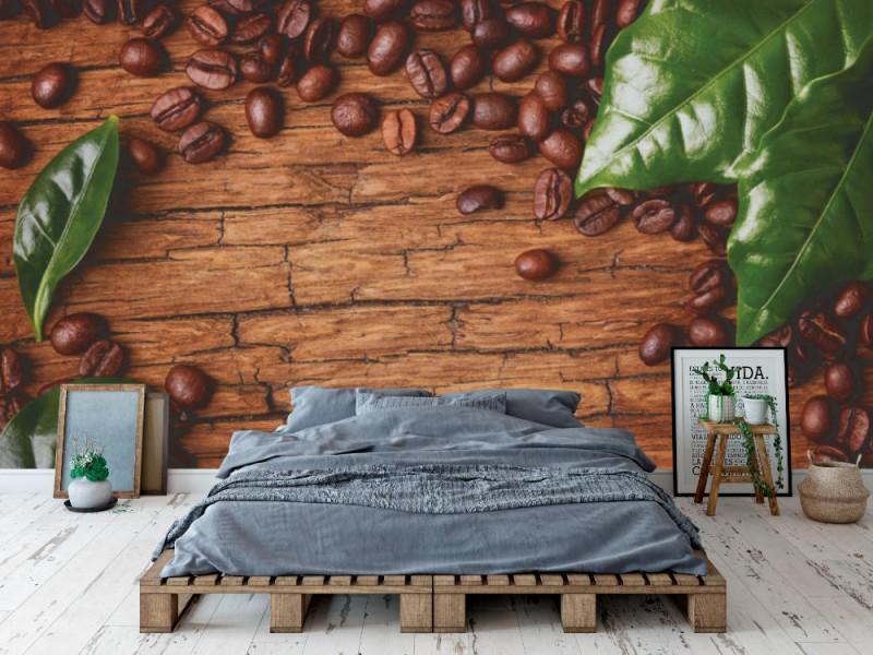Fototapet kaffebönor och gröna blad på träbakgrund (27945277)