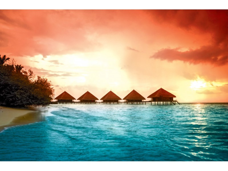Fototapet Bungalows med steg in i den fantastiska gröna lagunen