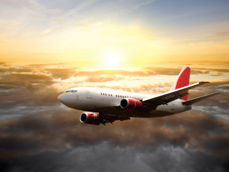 Fototapet flygplan i himlen vid solnedgången